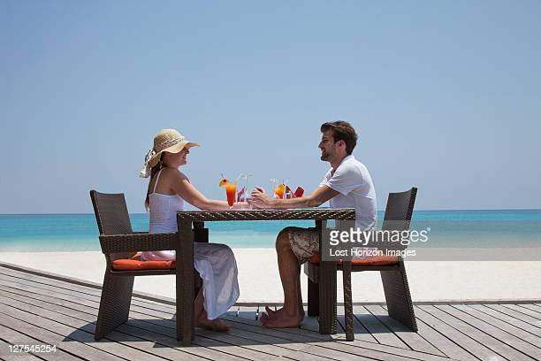 Couple eating together on deck at beach