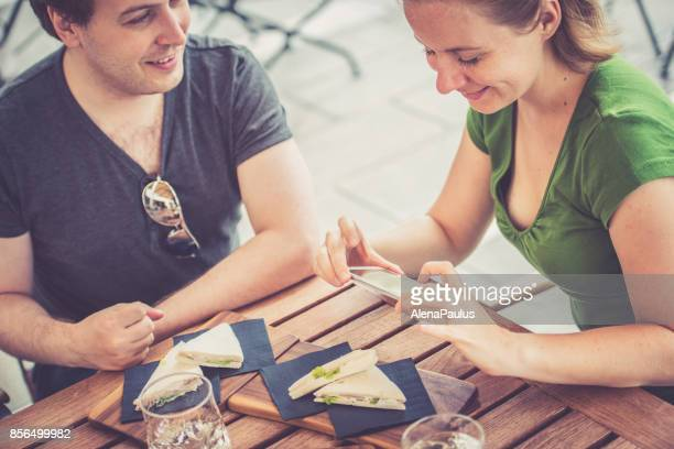 Couple eating tramezzini - italian sandwiches and taking food photos outdoors