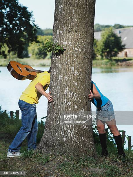 Couple either side of tree, heads obscured by trunk, man with guitar