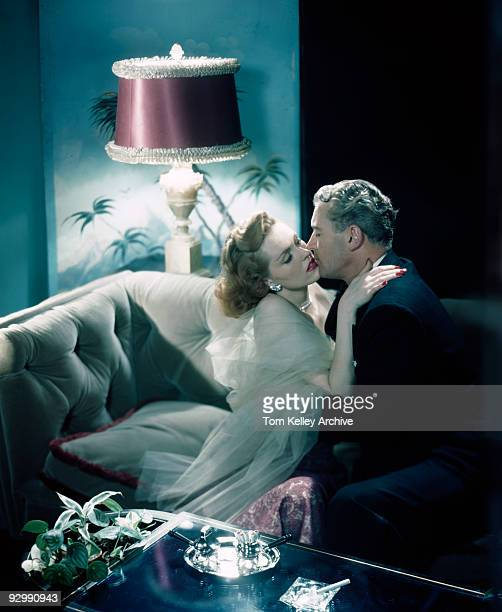 A couple elegantly dressed in formal wear exchange kisses while sitting on a couch 1947