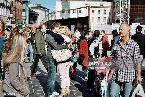 Couple embrace and kiss in a public space. Two young lovers show affection on a public street.