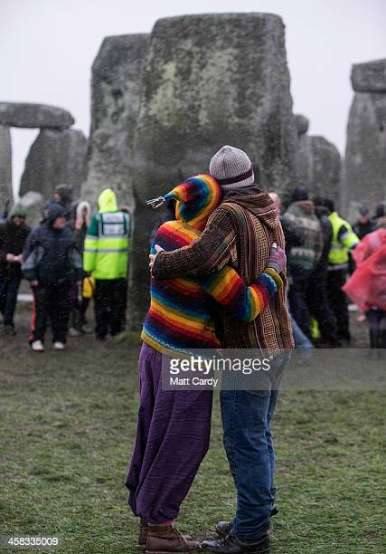 A couple embrace as druids pagans and revellers gather in the centre of Stonehenge hoping to see the sun rise as they take part in a winter solstice...