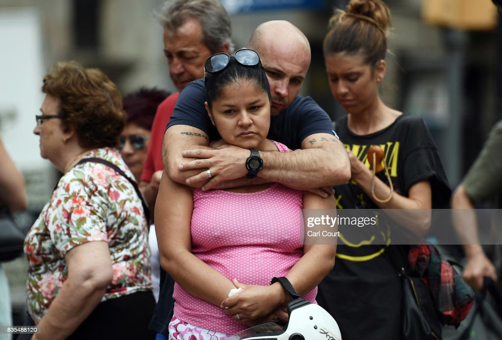 A couple embrace as they gather around tributes on Las Ramblas near the scene of Thursday's terrorist attack, on August 19, 2017 in Barcelona, Spain. A nationwide manhunt continues for Younes Abouyaaqoub, now named by Spanish media as the suspected driver in an attack that left thirteen people dead and dozens injured when a van was driven at crowds in the popular Las Ramblas area of Barcelona on Thursday.
