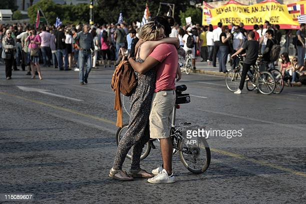 A couple embrace as they participate in a protest in front of the Greek parliament against a new austerity package in Athens on June 1 2011 ATHENS...