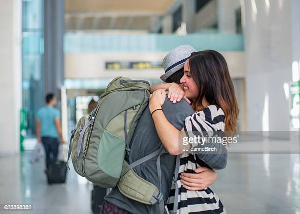 Couple embrace at airport arrival