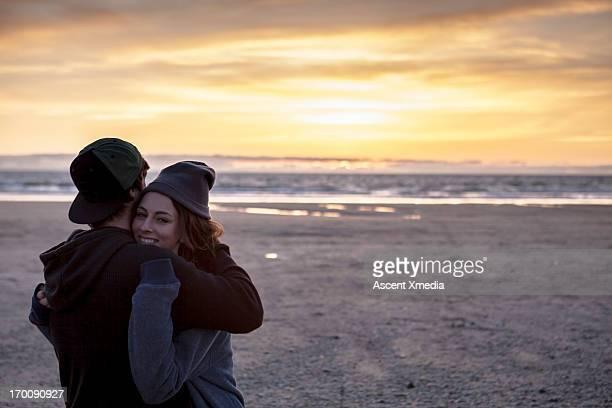 Couple embrace at beach, sunrise