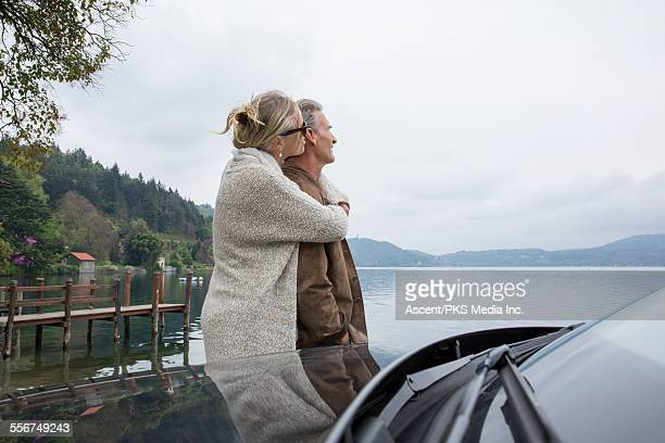 Couple embrace at edge of lake, beside car