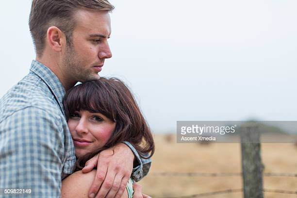 Couple embrace at edge of rural field, fog