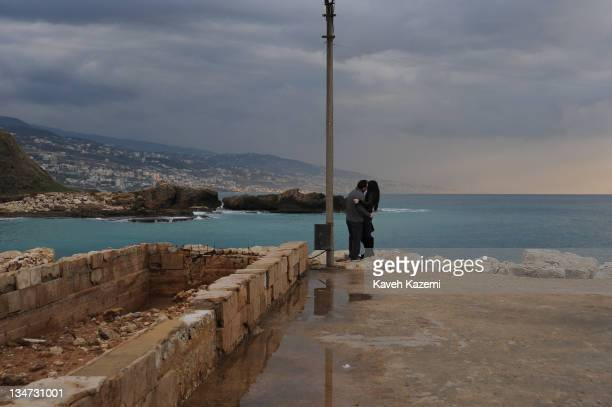 A couple embrace at sunset by the seafront in Byblos Lebanon 2011