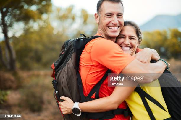 a couple embrace each other after finish a trekking trip. - mid adult stock pictures, royalty-free photos & images