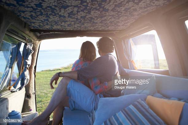 couple embrace in camper van on atlantic coastline. - dougal waters stock pictures, royalty-free photos & images