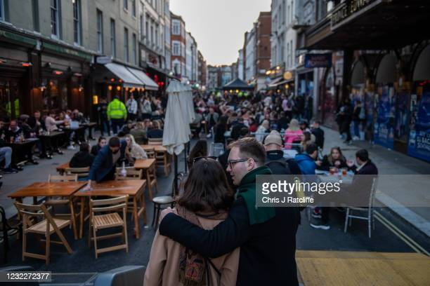Couple embrace in front of a street of people eating and drinking in Soho as non essential retail reopens on April 12, 2021 in London, United...