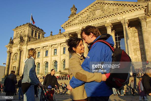 A couple embrace in front of the Reichstag October 3 2001 during celebrations in Berlin for the anniversary of German reunification On October 3 West...