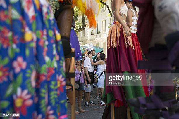 A couple embrace in the street near stilt walkers during the Bloco das Mulheres Rodadas Carnival parade in Rio de Janeiro Brazil on Wednesday Feb 10...