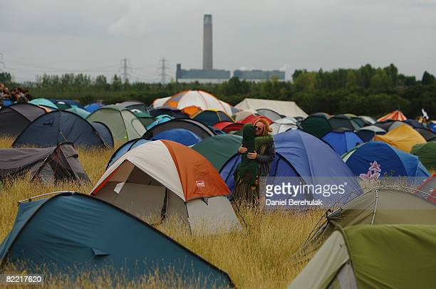 A couple embrace inside the Camp For Climate Action 2008 as the Kingsnorth Power Station is pictured in the background on August 8 2008 in Kingsnorth...