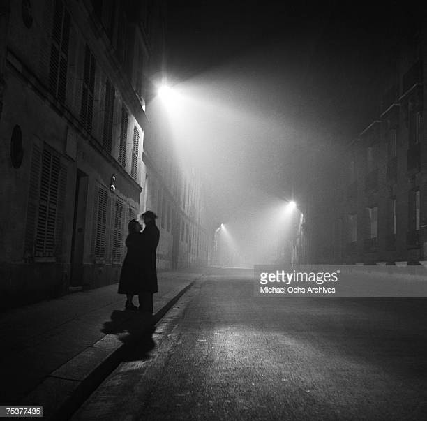 A couple embrace on a foggy street at night on November 1 1948 in Paris France