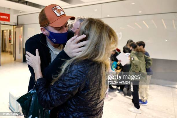 Couple embrace on arrival from the United States at Heathrow's Terminal 5 in west London on August 2, 2021 as quarantine restrictions ease. - People...