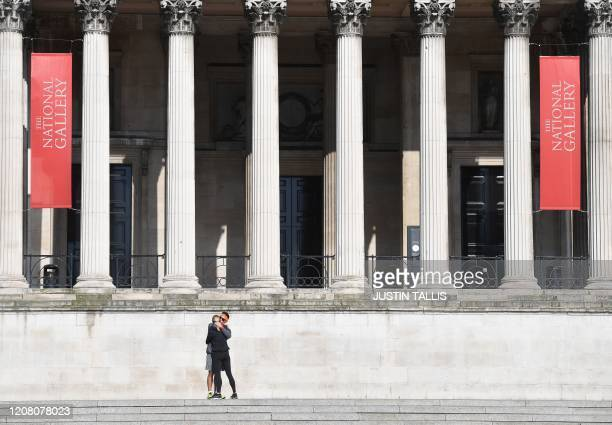 A couple embrace on the steps outside the National Gallery in Trafalgar Square in central London on March 24 2020 after Britain ordered a lockdown to...