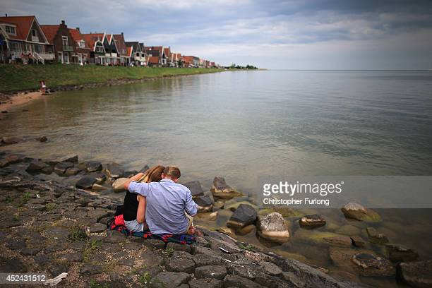 A couple embrace sitting at the waterside in the traditional Dutch town of Volendam as the Netherlands tries to come to terms with the tragedy of...