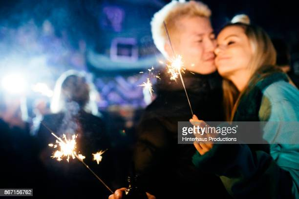 Couple Embrace While Holding Sparklers And Dancing In Nightclub