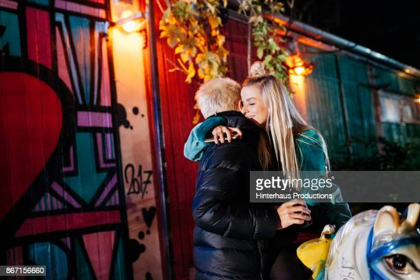 Couple Embrace While Riding Mechanical Horse At Open Air Nightclub