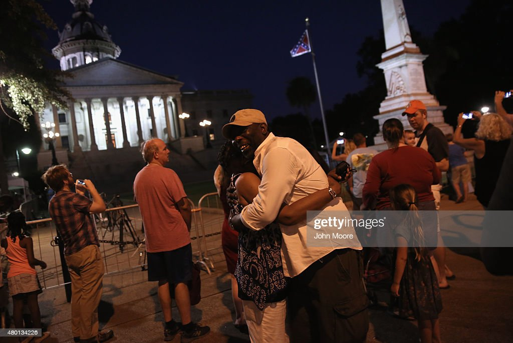 A couple embraces as the Confederate flag flies in front of the South Carolina statehouse on its last evening on July 9, 2015 in Columbia, South Carolina. South Carolina Governor Nikki Haley signed a bill to remove the Confederate flag from the statehouse grounds Friday morning.