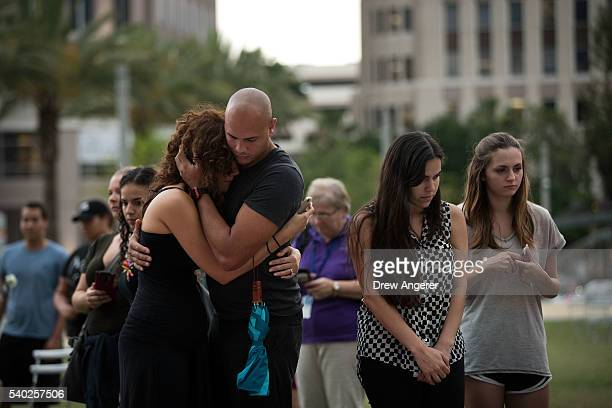 A couple embraces as they visit a memorial for the victims of the Pulse Nightclub shooting at the Dr Phillips Center for Performing Arts June 14 2016...