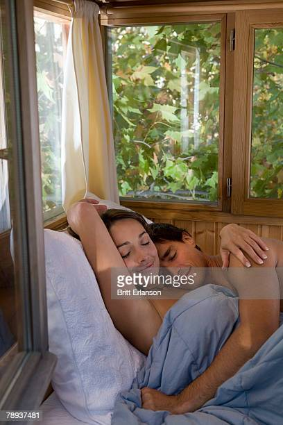 Couple embracing and sleeping in bed.