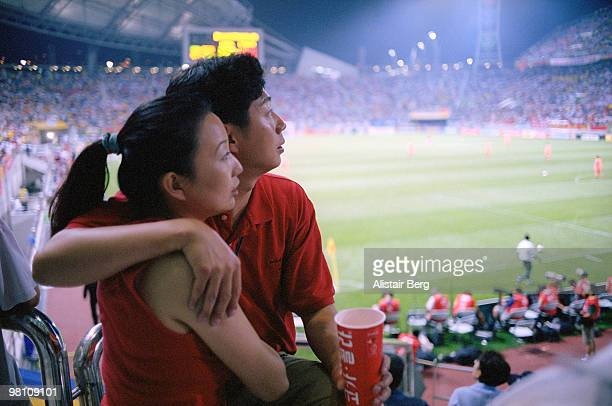 Couple embracing at a football match