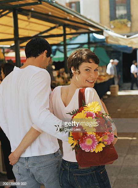 couple embracing at market, portrait of woman, rear view - david ramos fotografías e imágenes de stock