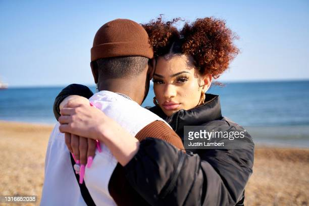 couple embracing at the beach looking to camera - couple relationship stock pictures, royalty-free photos & images