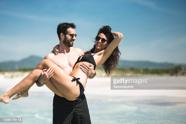 couple embracing at the seaside - picking up stock pictures, royalty-free photos & images