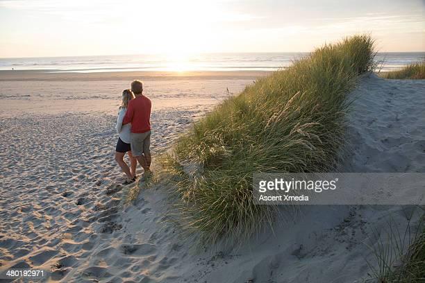 Couple embracing below sand dune