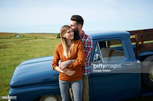 Couple embracing beside old fashioned truck in countryside.