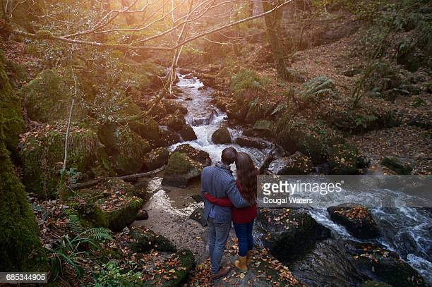 Couple embracing beside woodland stream.