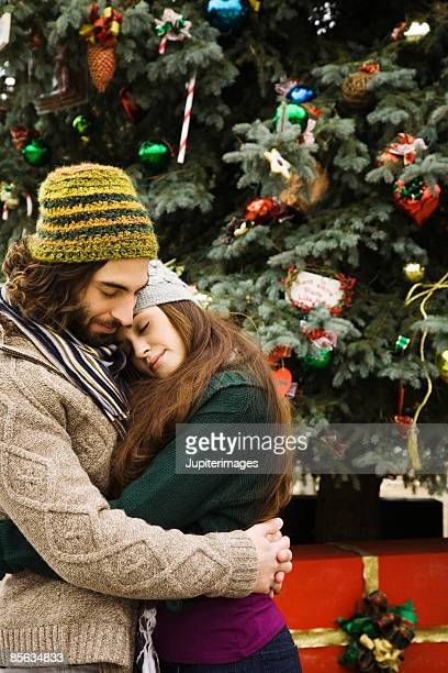 Couple embracing by Christmas tree