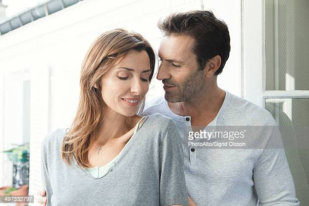 Couple embracing by open window