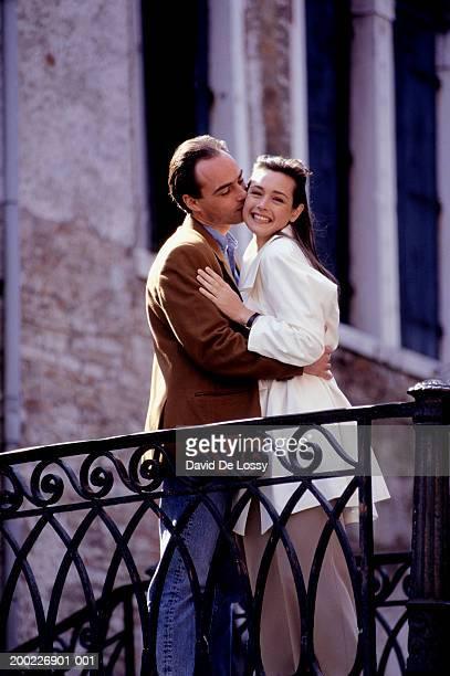 couple embracing by railings, three quarter length - three quarter length ストックフォトと画像