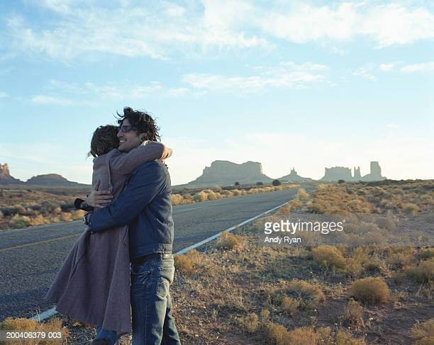 Couple embracing by road in desert, man smiling