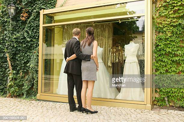 Couple embracing by shop window containing wedding dresses, rear view