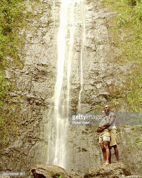 couple embracing by waterfall, smiling - water fall hawaii stock pictures, royalty-free photos & images