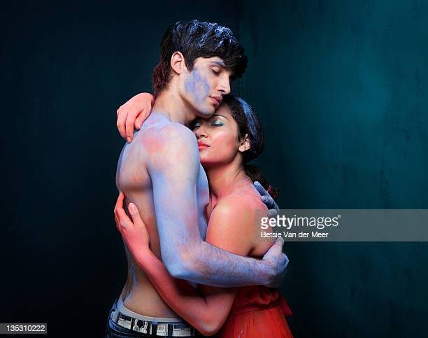 Couple embracing, covered in coloured powders.