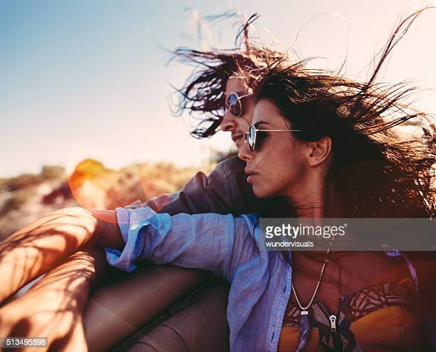 Couple embracing during road trip in back seat of convertible