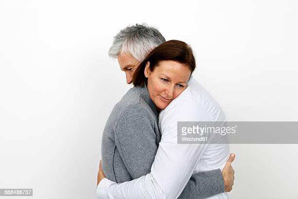Couple embracing each other in front of white background