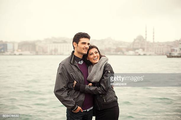 Couple Embracing Each Other Near The Sea with City View