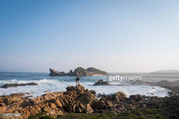 couple embracing each other stand on rocky coastline at beach against sky - wide shot stock pictures, royalty-free photos & images
