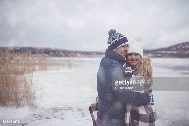 Couple embracing in a winter in a warm checkered blanket