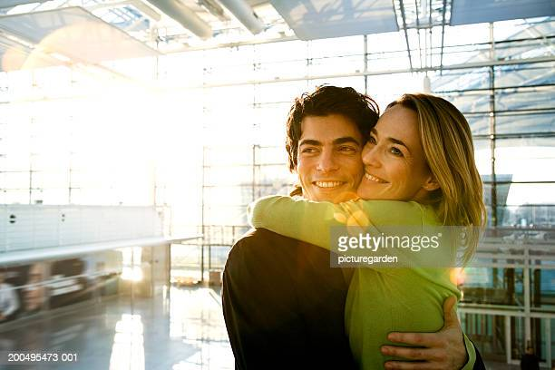 Couple embracing in airport, smiling