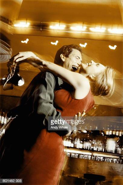 Couple embracing in bar, laughing, woman holding shoes