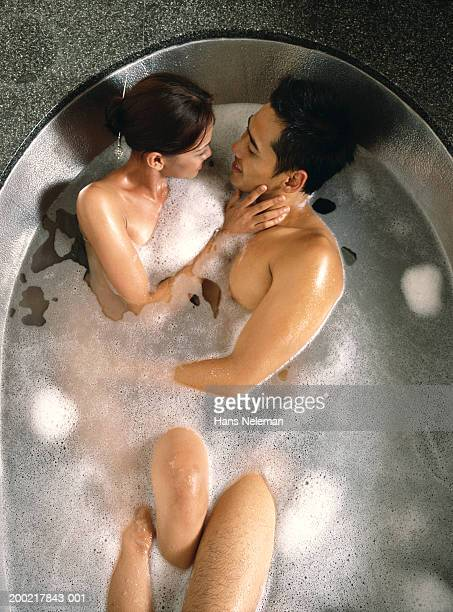 Couple embracing in bath, overhead view